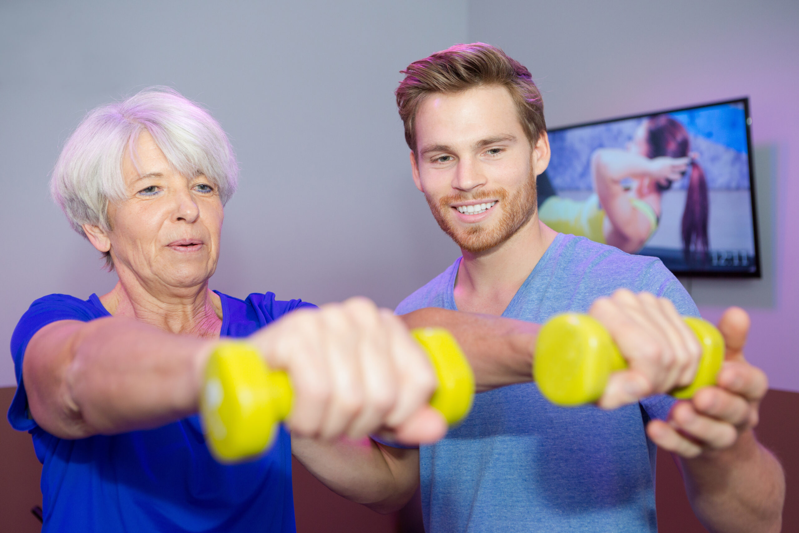 male coach with senior woman with dumbbells