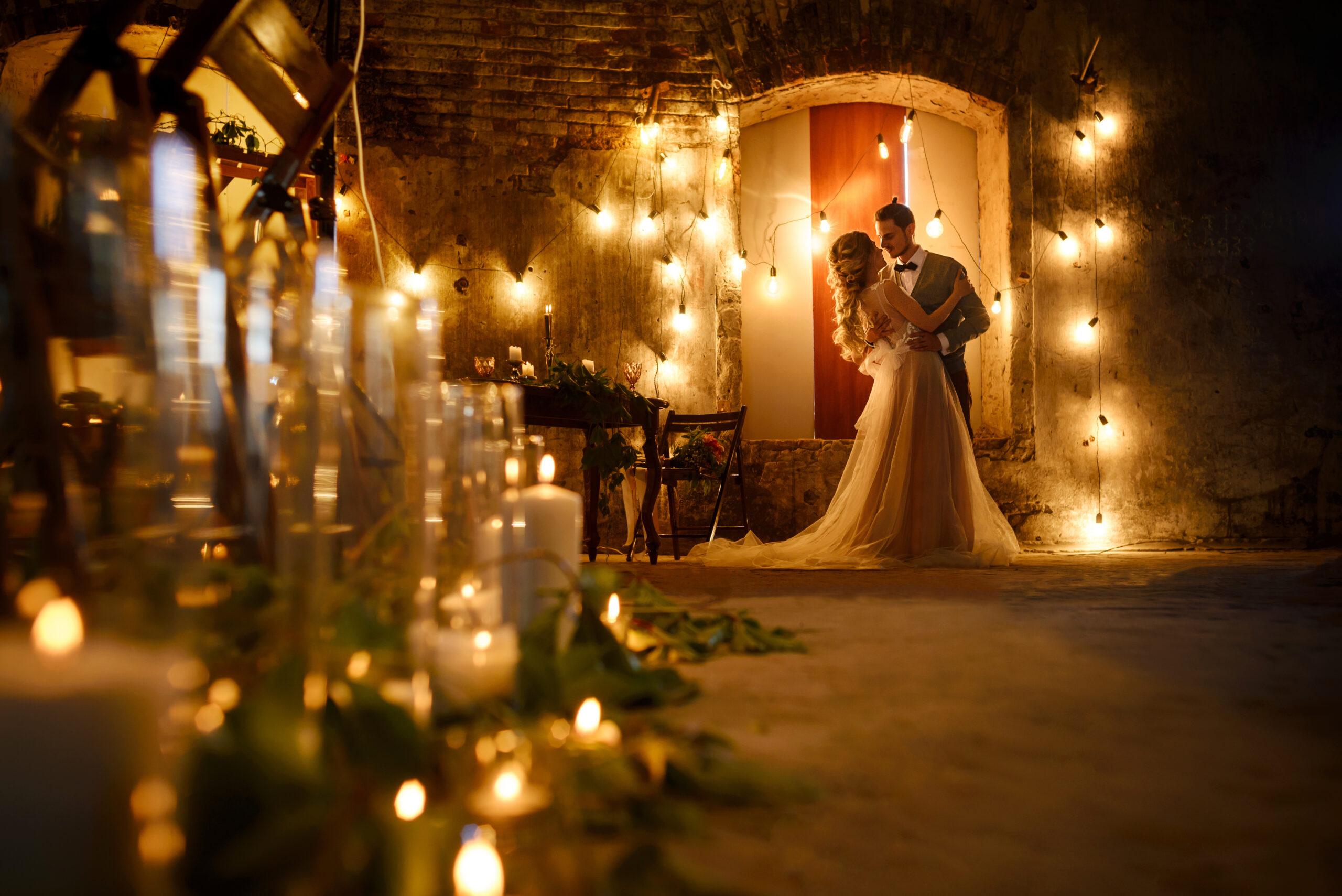 Stylish hipster wedding couple in romantic loft decorations at night